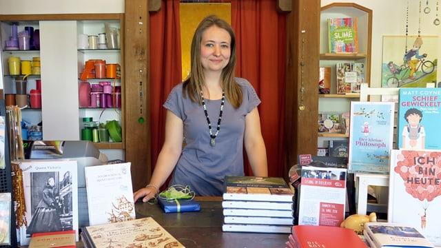 Eine junge Frau steht in einem Buchladen hinter einem Tisch voller Bücher.