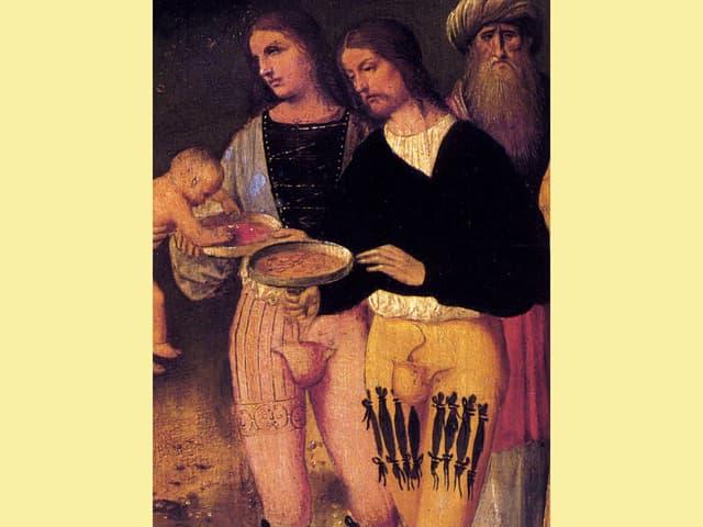 Zwei Männer in eng anliegenden Strumpfosen füttern ein Kind.