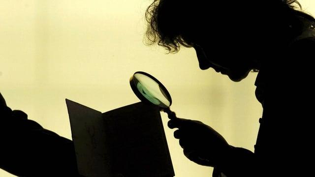 Eine Frau untersucht ein Buch mit einer Lupe.