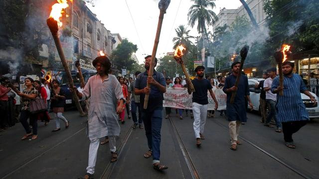 Männer mit Fackeln führen auf der Strasse eine Menschenmenge an.