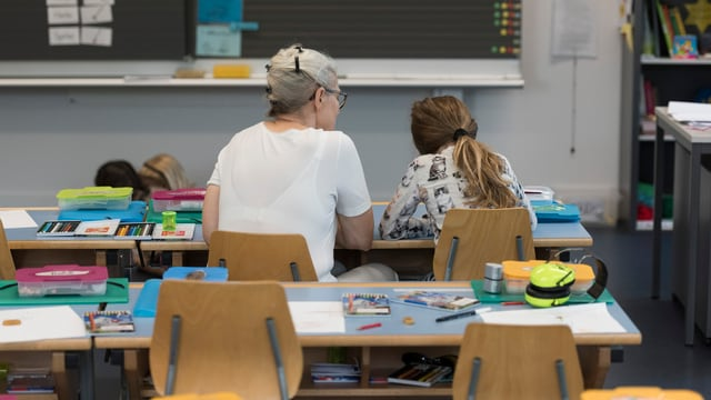 Lehrerin sitzt mit Schülerin in Schulzimmer