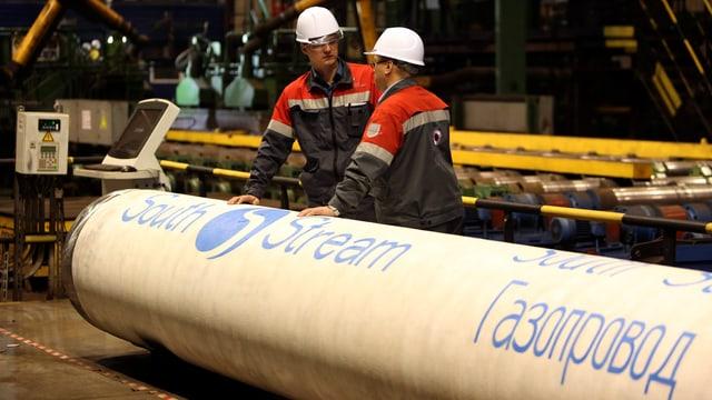 Russische Arbeiter an einem mit kyrilischen Zeichen beschrifteten Rohr.
