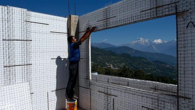Ein Arbeiter erstellt an einem neuen Haus in Nepal eine Wand aus Karbon, um künftig vor Erdbeben besser geschützt zu sein. (keystone)