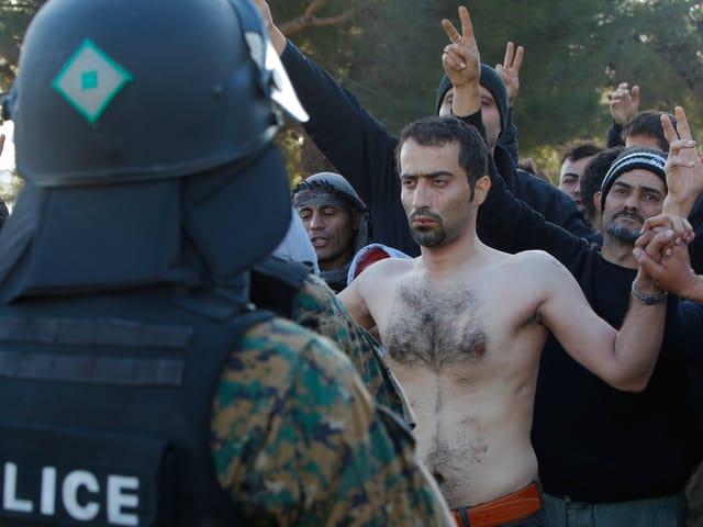 Ein Iraner hat sich an der griechisch-mazedonischen Grenze den Mund zugenäht. Weiter Männer stehen um ihn herum und protestieren leise. (reuters)