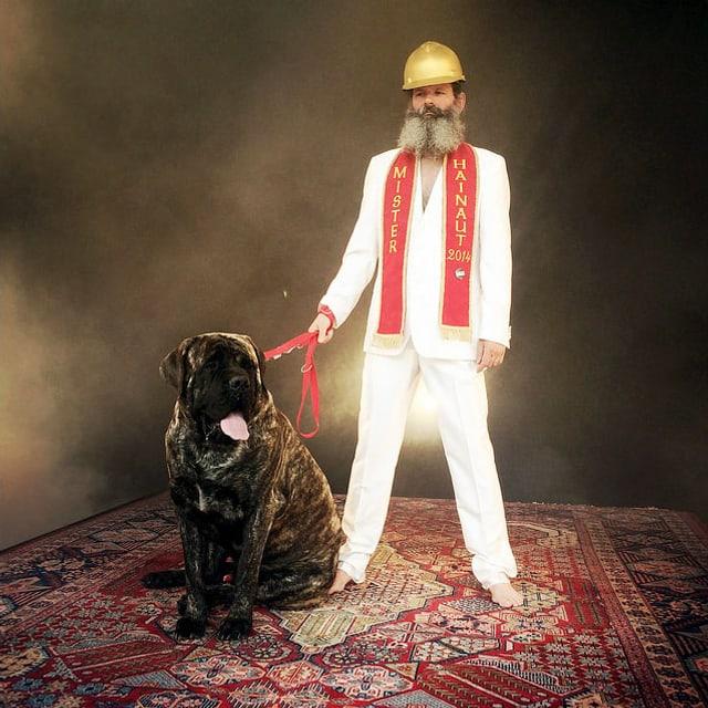 Mann in weissem Anzug mit goldenem Helm und grossem Hund steht auf fliegendem Perserteppich.