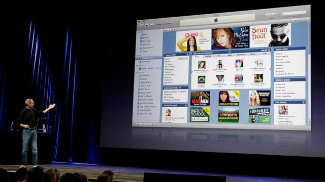 Steve Jobs steht vor einer Präsentation mit einem iTunes Screenshot.