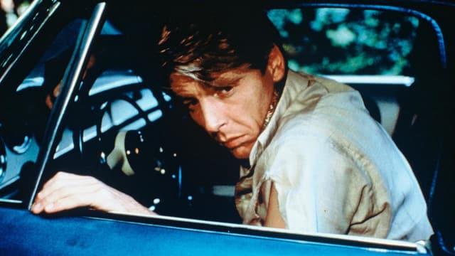 Ein Mann mit aufgerissenem Ärmel sieht durch das Seitenfenster eines Autos.