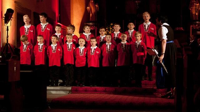 Ein Chor mit Chorknaben in roten Sennenhemden.