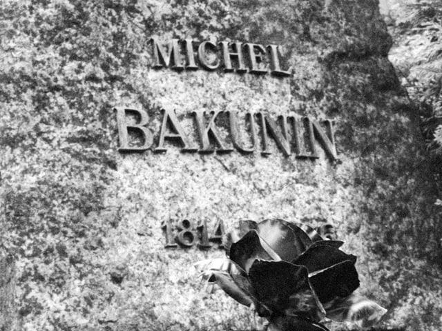 Schriftzug «Michel Bakunin» auf seinem Grabstein in Bern, davor eine Rose, Bild schwarz-weiss.