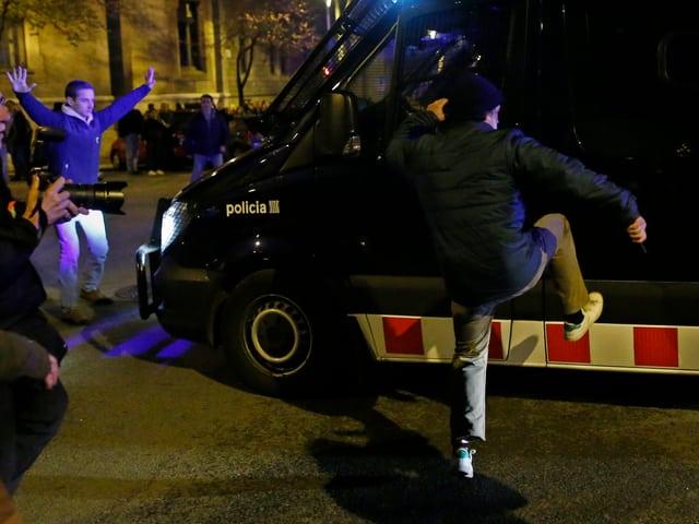 Demonstrant tritt Polizeiauto.