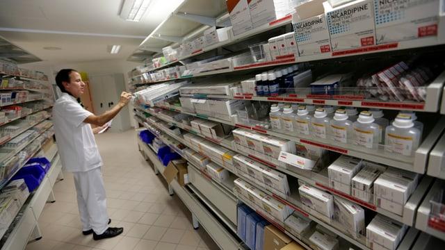 Ein Mann steht vor einerm mit Medikamenten gefüllten Regal.