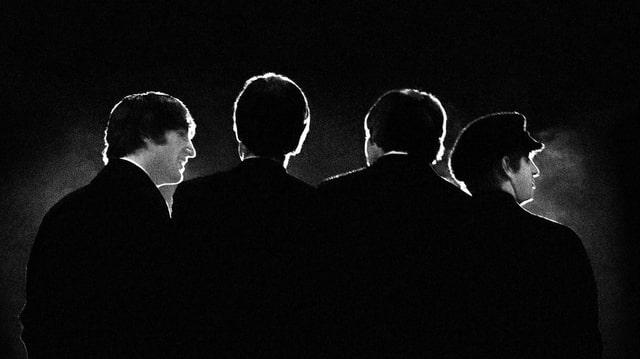 Die Beatles von hinten fotografiert, alles sehr dunkel.