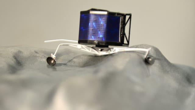 Ein Modell des Landegeräts Philae auf einem grauen Untergrund.