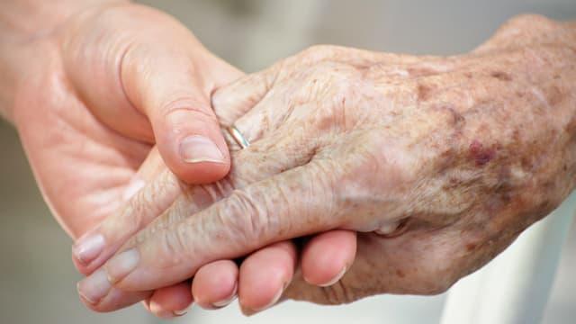 Eine junge Frau hält die Hand einer alten Frau.