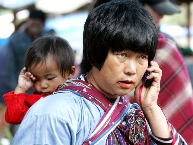 Frau mit Baby auf dem Rücken telefoniert mit den Handy.