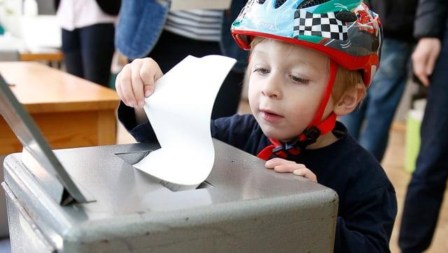 Ein Junge steckt den Abstimmungszettel seines Vaters in die Urne.