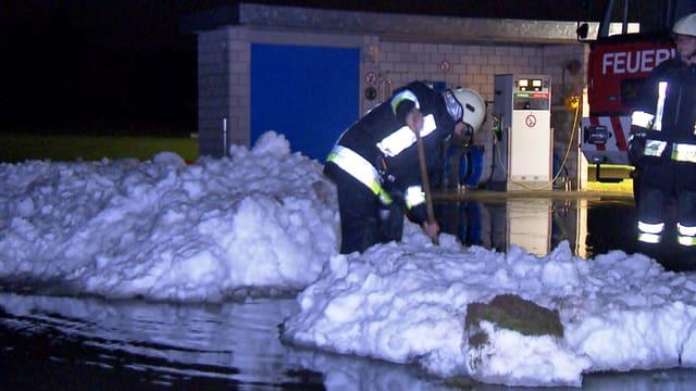 Feuerwehrmann schaufelt zwischen Schneehaufen und Wasserlachen.