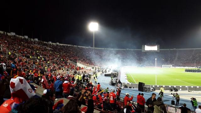 Blick in ein Fussballstadion bei Nacht mit rot gekleideten Fans.