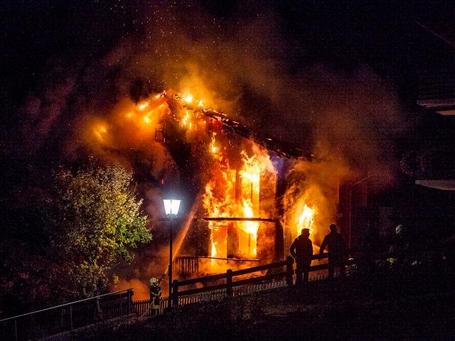 Brennendees Haus, ein Feuerwehrmann bekämpft die Flammen.