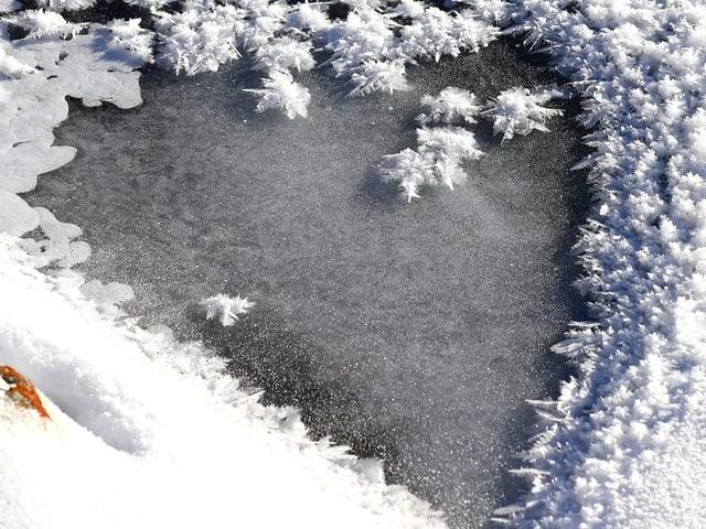 Eis mit Schneekristallen in Herzform