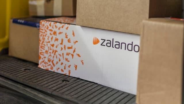 Pakete, u.a. eines von Zalando, im Fonds eines Post-Lieferwagens.