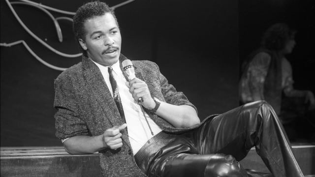 Ein schwarzer Mann sitzt mit einem Mic in der Hand auf einer Bühne.