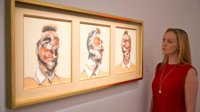 Frau steht vor dem dreigeteilten Gemälde von Francis Bacon