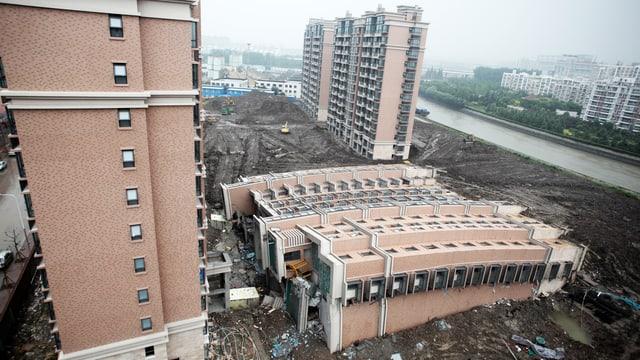 Wohngebäude, das umgekippt am Boden liegt.