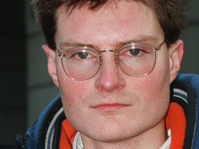 Christoph Meili im Jahr 1997 vor dem damaligen SBG-Logo, nach seinem Fund von Akten nachrichtenloser Vermögen, die vernichtet werden sollten.