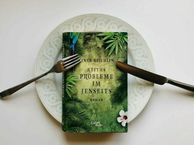 Der Roman «Keiths Probleme im Jenseits» von Linus Reichlin liegt auf einem Teller.