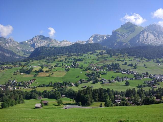 Blick auf Wildhaus mit Bergen im Hintergrund.
