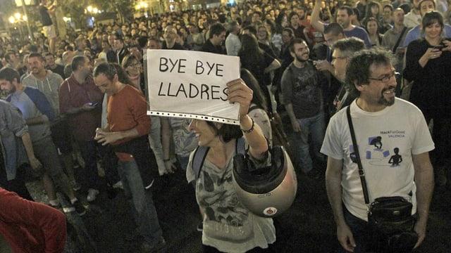 Eine Frau hält ein Plakat mit der Aufschrift «Bye bye Diebe» in die Höhe.