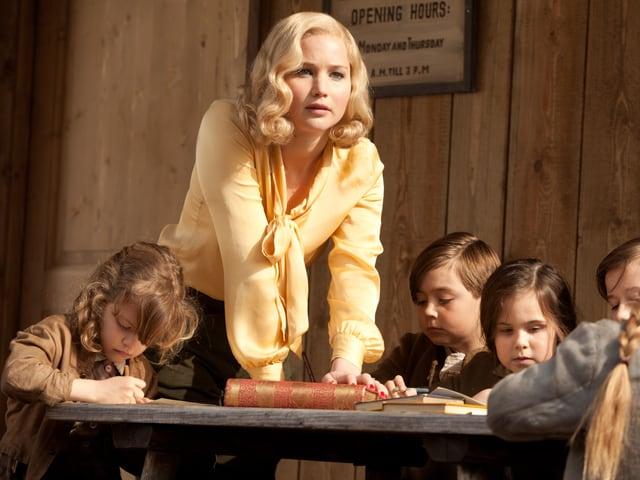 Lawrence lehnt auf einen Tisch, an dem mehrere Kinder sitzen.