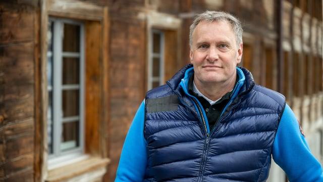 Ein Mann blickt freundlich in die Kamera. im Hintergrund ist ein Holzhaus zu erkennen.