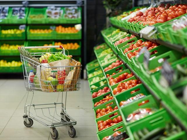 Gemüseablage im Laden mit Einkaufswagen davor