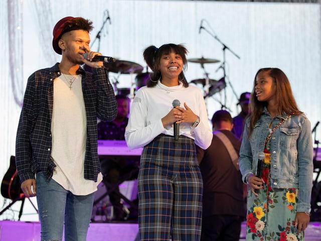 Drei Jugendliche auf eine Bühne.