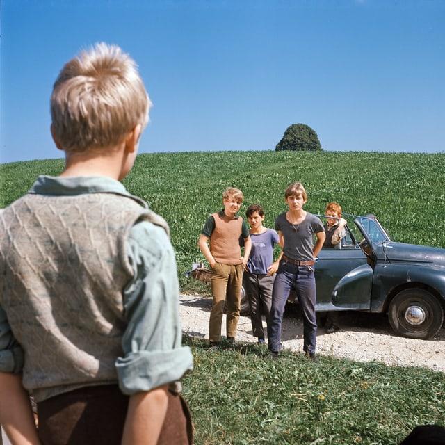 Einer der Kummerbuben blickt zu vier anderen, welche vor einem VW Käfer Cabriolet stehen.