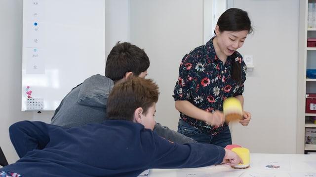 Zwei Jungen strecken sich, um mit Hämmern aus Plüsch ein Kärtchen auf einem Tisch zu erreichen. Eine stehende Frau holt ebenfalls mit einem solchen Hammer aus.