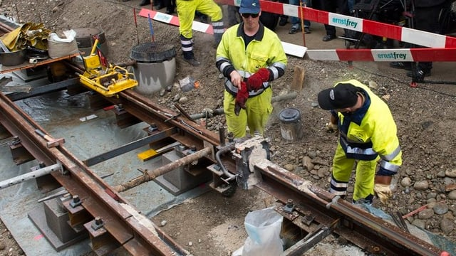 Bauarbeiter stehen vor offenem Tramgleis