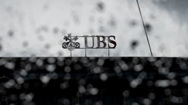 UBS Logo hinter verregneter Scheibe.