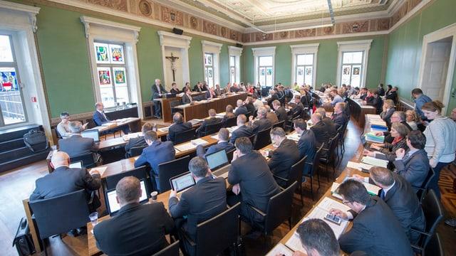 Ein Parlamentssaal von hinten mit sitzenden Männern und Frauen.