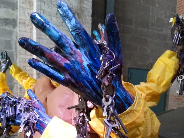An einer blauen Hand hängen zahlreiche Schlüssel