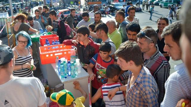 Helfer verteilen vor Bahnhof Wasser an Flüchtlinge.