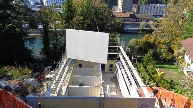 Ein Kran fügt eine Holzwand in das neue Gebäude für Musikstudenten in Luzern ein.