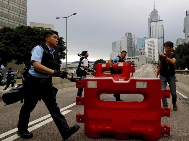 Polizisten räumen eine Strassenblockade weg. Ein Mann spricht sie an.