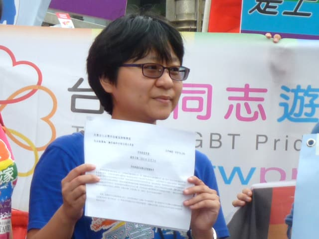 Eine junge Frau hält ein Blatt Papier vor ihrem Oberkörper.