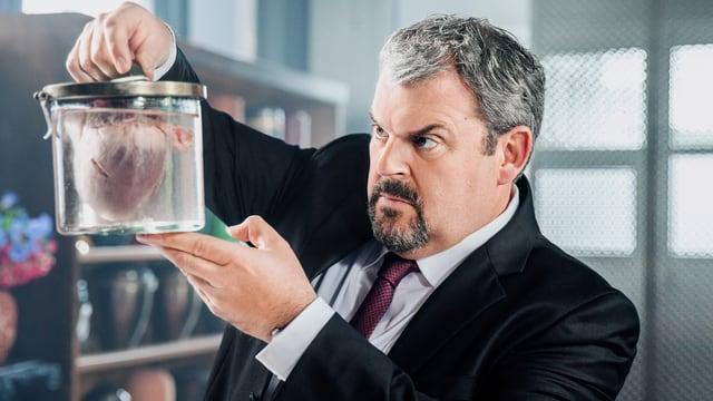 Bestatter Luc Conrad hält Glasbehälter mit Herz in der Hand.