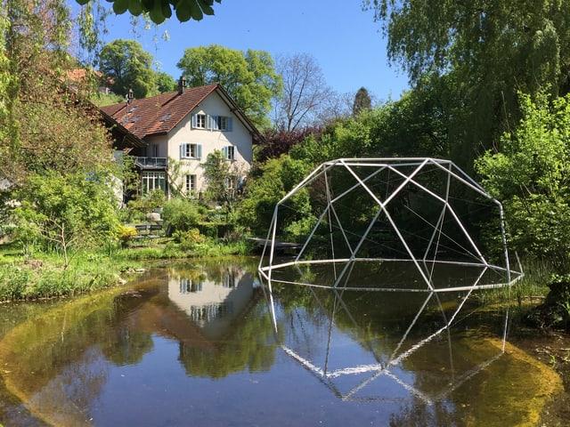 Skulptur schwimmt im Teich vor einem Haus.