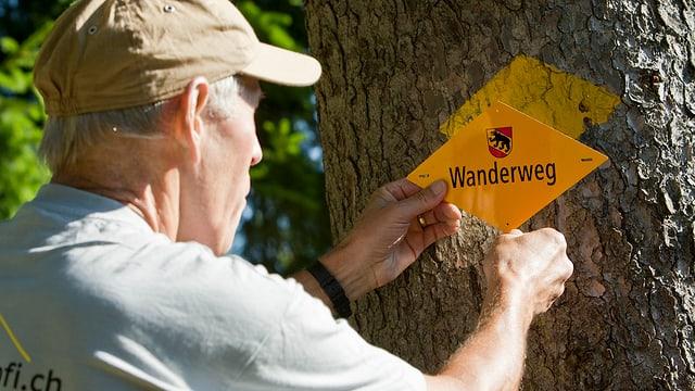 Ein älterer Mann mit Schirmmütze befestigt ein Wanderweg-Zeichen an einem Baum.
