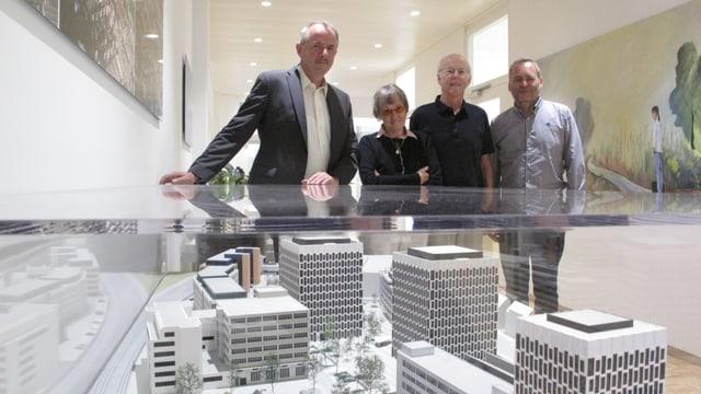 Vier Personen hinter Glasvitrine mit Modellhäusern